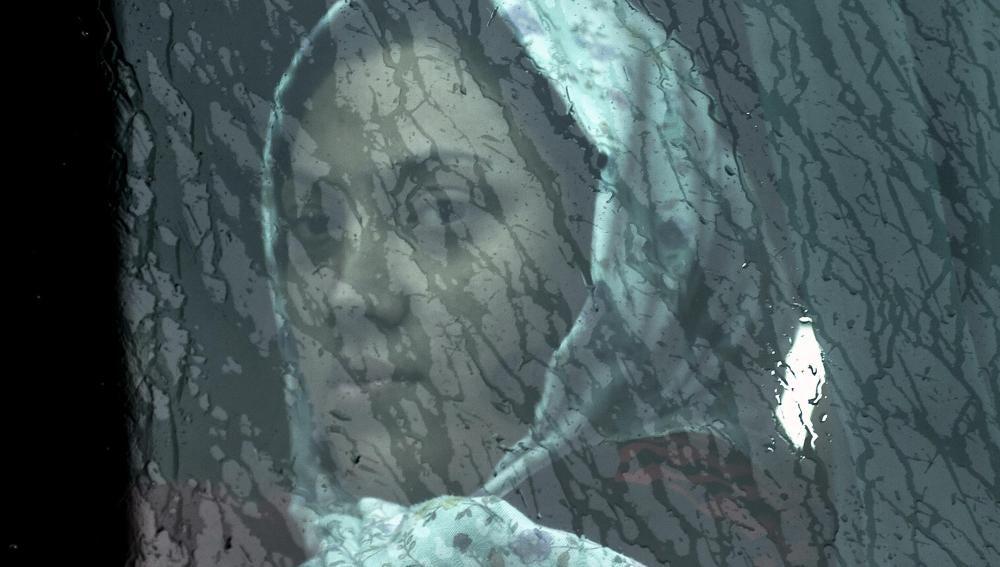 Una mujer inmigrante mira a través de la ventana
