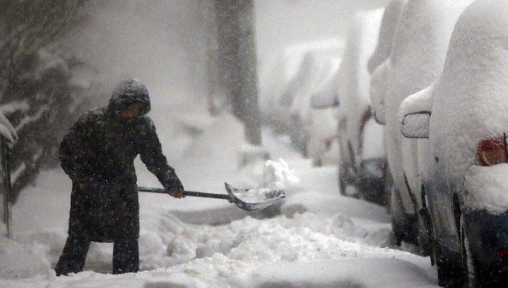 Una persona intenta retirar la nieve de la calle en Nueva York