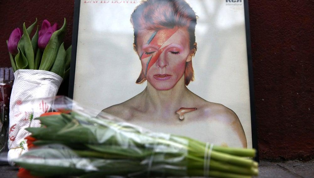 Homenaje a David Bowie frente al mural del cantante en Londres