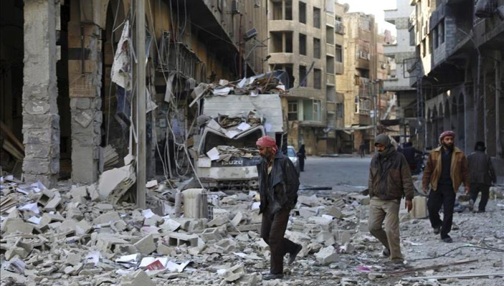 Varias personas caminan entre los escombros a las afueras de Damasco