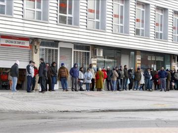 Varias persona forman una cola ante una oficina del INEM