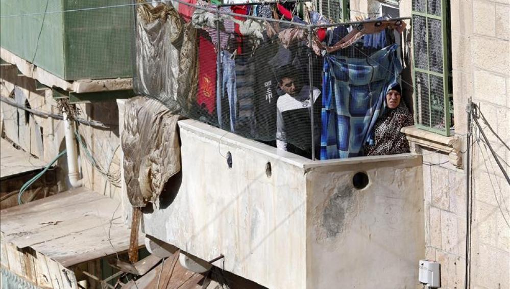 Palestinos observan una evacuación desde el balcón de su casa