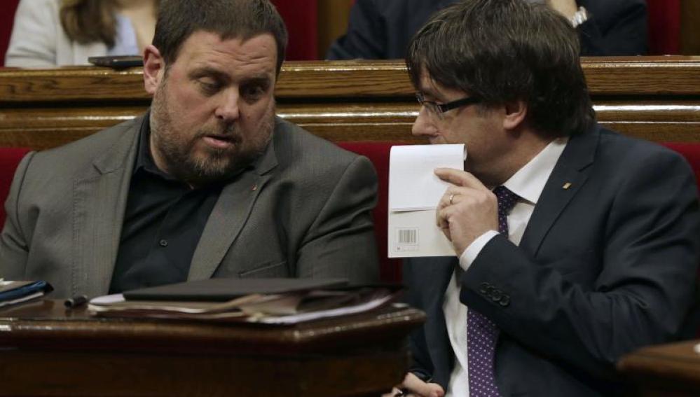 El presidente de la Generalitat, Carles Puigdemont conversa con el vicepresidente Oriol Junqueras