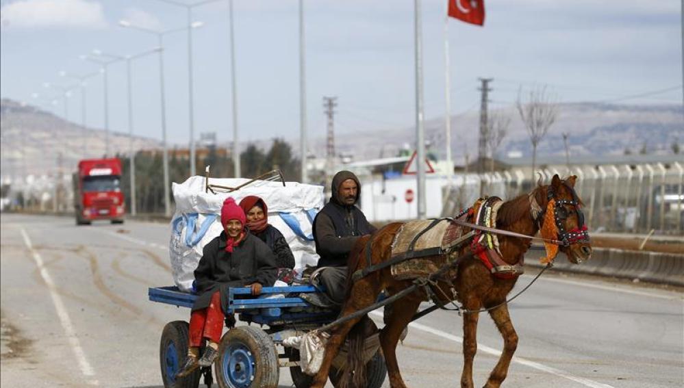 Refugiados viajan este domingo entre la frontera turco-siria.