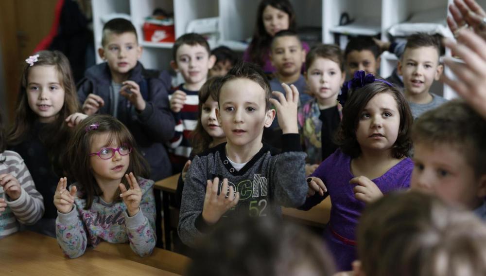 Los alumnos de una clase aprenden lengua de signos para comunicarse con un compañero sordo