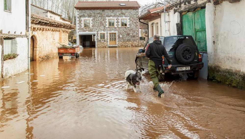Un vecino de la localidad burgalesa de Puentedura atraviesa una zona inundada tras la crecida del río Arlanza