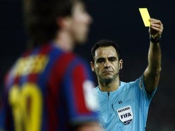 Velasco Carballo muestra amarilla a Leo Messi durante un partido de 2010