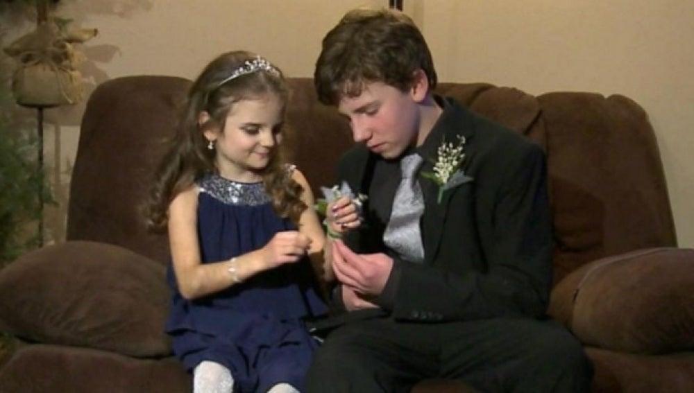 El adolescente junto a su hermana pequeña preparada para ir al baile de instituto