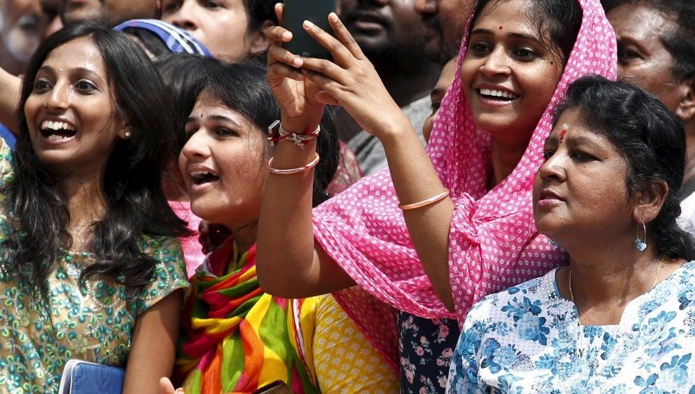 Una mujer india intenta hacer una foto con su móvil