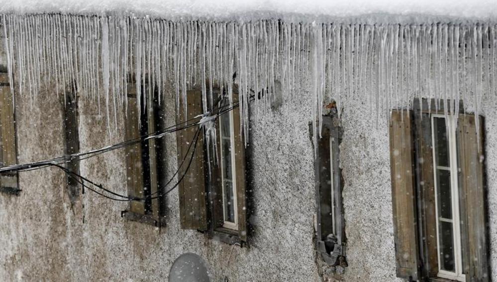 Carámbanos de hielo penden de la cornisa de un tejado