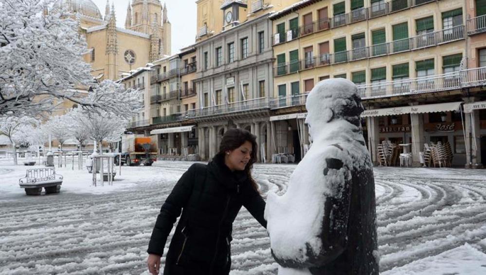 Una mujer retira la nieve sobre la escultura del poeta Antonio Machado, en la Plaza Mayor de Segovia