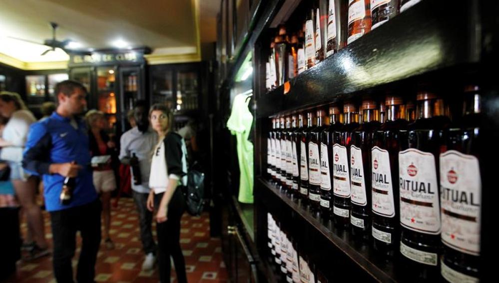 Turistas observan varias botellas de ron en La Habana