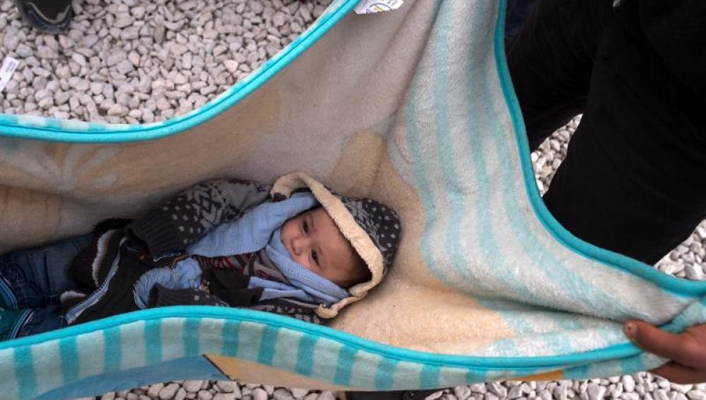 Un bebe descansa en una manta mientras refugiados esperan subir a bordo de un tren en Macedonia