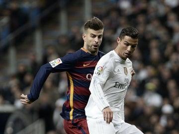 Piqué y Cristiano disputan por el balón en el Bernabéu