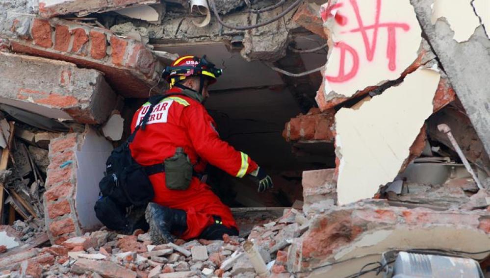 Un bombero busca víctimas entre los escombros