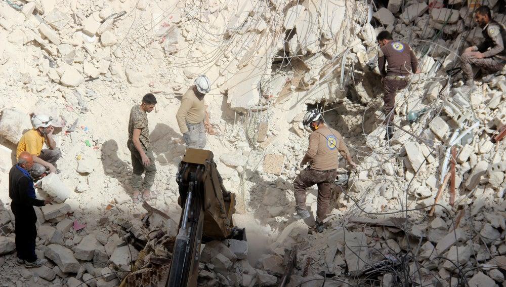 Miembros de los equipos de rescate buscan entre los escombros