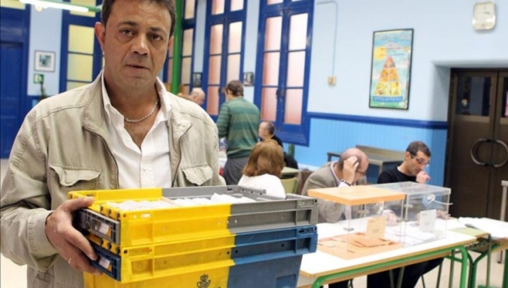 Un empleado de Correos entregando los votos en un colegio electoral