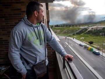 Un vecino contempla el fuego del incendio desde su casa.