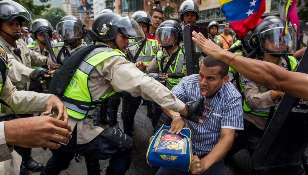 Miembros de la Policía Nacional Bolivariana forcejean con un manifestante