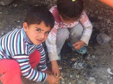 Dos niños recogen comida del suelo en Idomeni