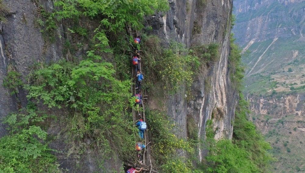 Niños chinos escalan roca para ir al colegio