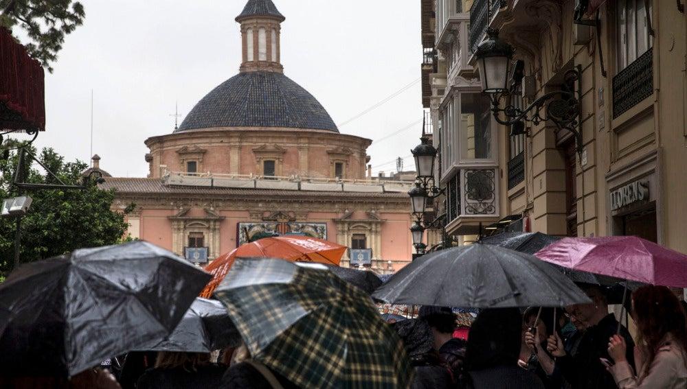 Gente protegiéndose de la lluvia