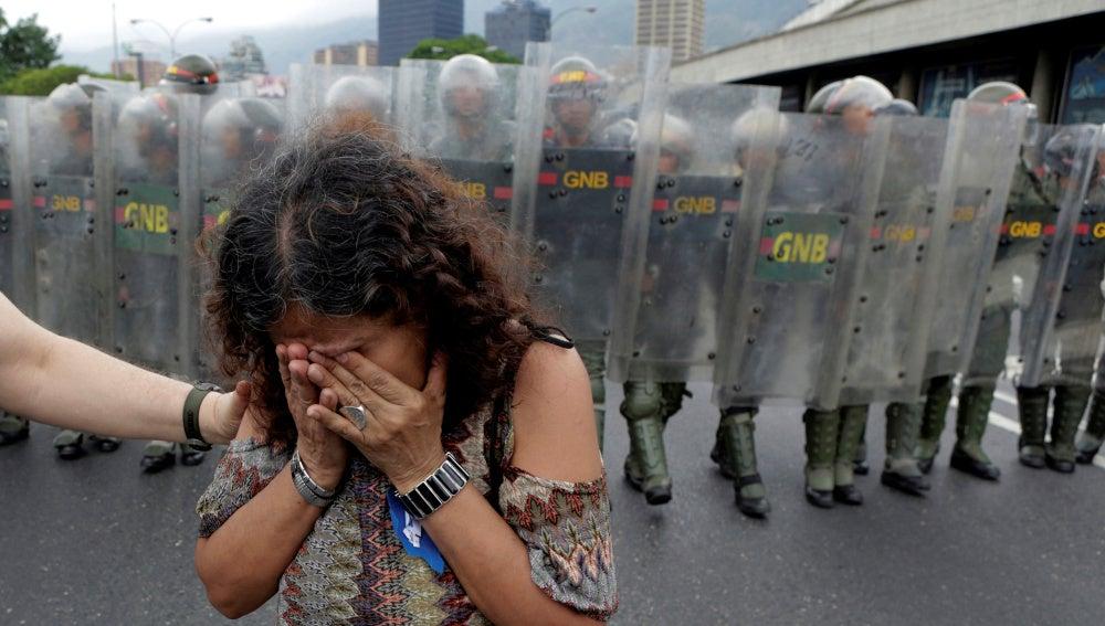 Una mujer llora en Venezuela frente a la Policía