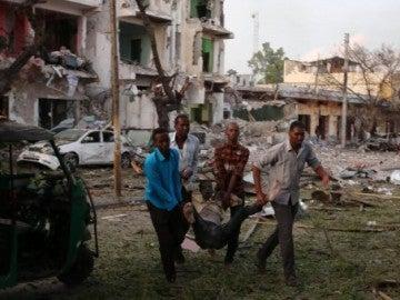 Cuatro hombres evacuan a un herido por el atentado en el Hotel Ambassador de Mogadiscio