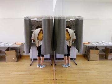 Un elector con su imagen reflejada en un espejo elige su papeleta para ejercer su derecho al voto en el Centro Cultural Volturno, en la localidad madrileña de Pozuelo de Alarcón.