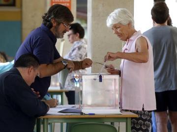 Una mujer deposita su voto en una urna de un colegio electoral