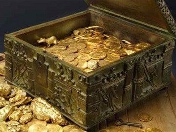 Un cofre lleno de monedas - Imagen de archivo