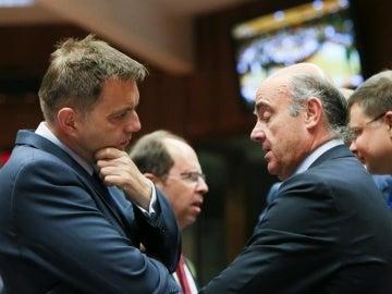 El ministro español de Economía y Competitividad en funciones, Luis de Guindos (d), conversa con el ministro eslovaco de Finanzas, Peter Kazimir