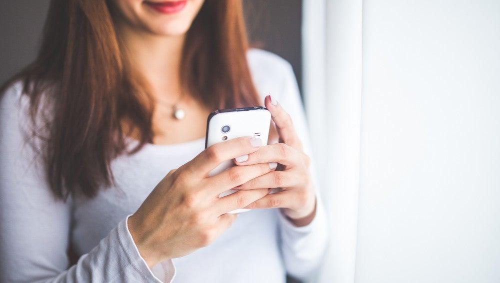 Mujer escribe en su teléfono móvil
