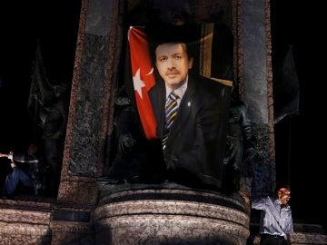 Un manifestante ondea una bandera con la foto del presidente turco Tayyip Erdogan durante una manifestación pro Gobierno en la plaza Taksim en Istanbul.