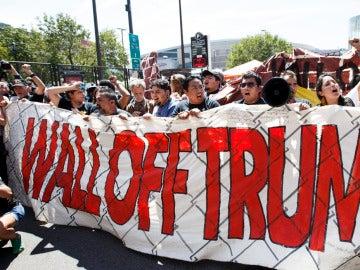 """Manifestantes con una pancarta que pone: """"Amurallar a Trump"""""""