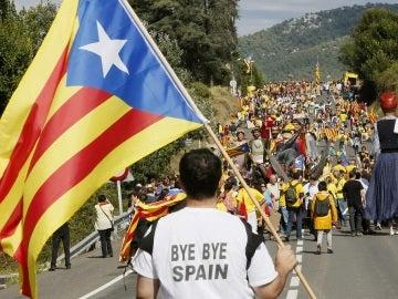 Un hombre porta una bandera independentista junto a un grupo de personas que participa, en una concentración a favor de la independencia de Cataluña.