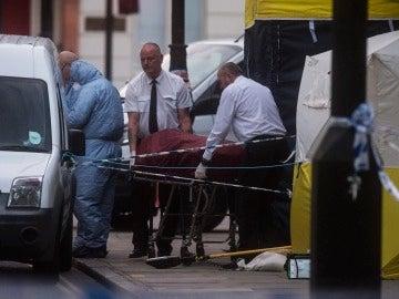 Investigadores retiran un cuerpo en la escena donde una mujer murió en Londres