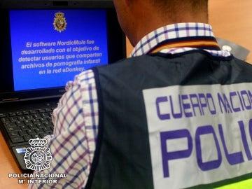 Un agente de Policía revisa un ordenador en el marco de una operación contra la pornografía infantil.
