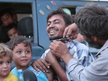Un sirio corta su barba tras la liberación de Manbij