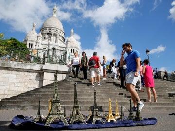 Un turista camina delante de la iglesia de Sacre Coeur de Montmartre en París durante el mes de agosto.
