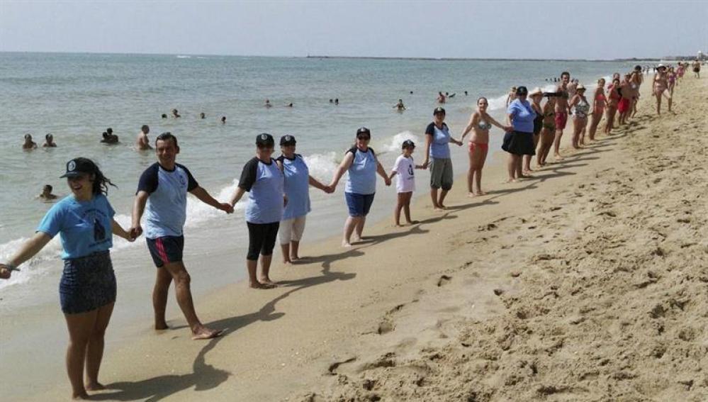 Cadena humana de más de cinco kilómetros en protesta a la violencia machista, en Isla Cristina