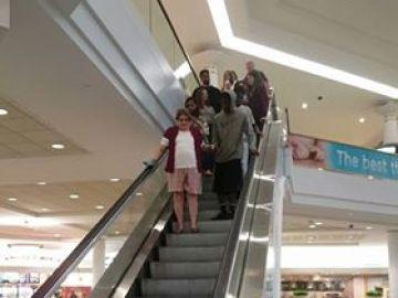 Joven ayudando a una anciana a bajar las escaleras mecánicas