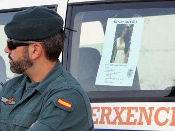 Un efectivo de la Guardia Civil junto al cartel de la joven Diana Quer
