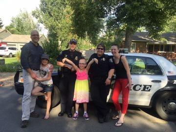 La niña junto a su familia y los dos agentes de policía