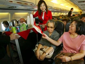 Una auxiliar de vuelo atendiendo a una pasajera