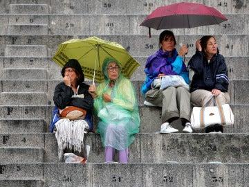 Gente protegiéndose de la lluvia con paraguas y chubasqueros