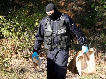 Un policia francés traslada material encontrado en un zulo de ETA en Riviere,