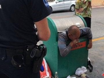 Hombre atrapado en el contenedor de basura