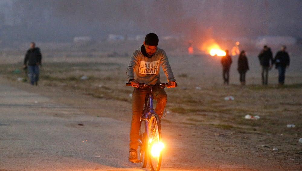 Un niño en bicicleta en el campamento de Calais