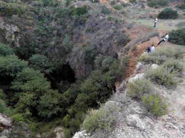 Varios cámaras de televisión toman imágenes de la sima donde agentes del Servicio de Protección de la Naturaleza (Seprona) han localizado el cadáver desnudo de una joven en las inmediaciones de la localidad valenciana de Chella